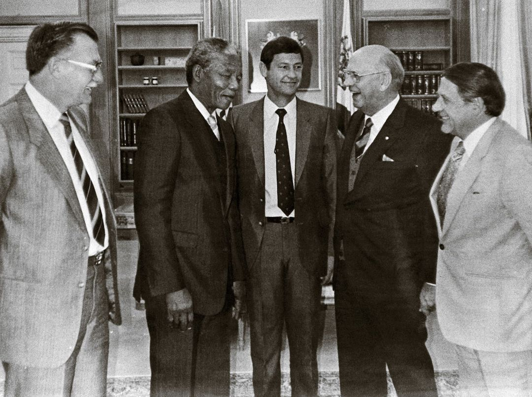 This very first meeting between Nelson Mandela, then still a prisoner, and State President PW Botha (2nd from right) happened in July 1989. This took place after many requests from Mandela over the years to meet the President in the hope of laying the groundwork for formal negotiations. PW had steadfastly refused such a meeting. Instead, the State President had sanctioned first his Minister of Justice, Prisons and Police, Kobie Coetsee, and then later a secret negotiating committee of senior government officials, to meet with Mandela. Also, in this photo are General Willemse (the Commissioner of Prisons), Dr Niël Barnard (the head of the National Intelligence Service) and Minister Kobie Coetsee. Just the day before, a tailor made the suit that Mandela is wearing. Mandela was also presented with a shirt, tie, shoes and underwear for this meeting. This was Mandela's second set of such clothing – he had first received a suit for his meeting with the Commonwealth Eminent Persons Group in 1986.