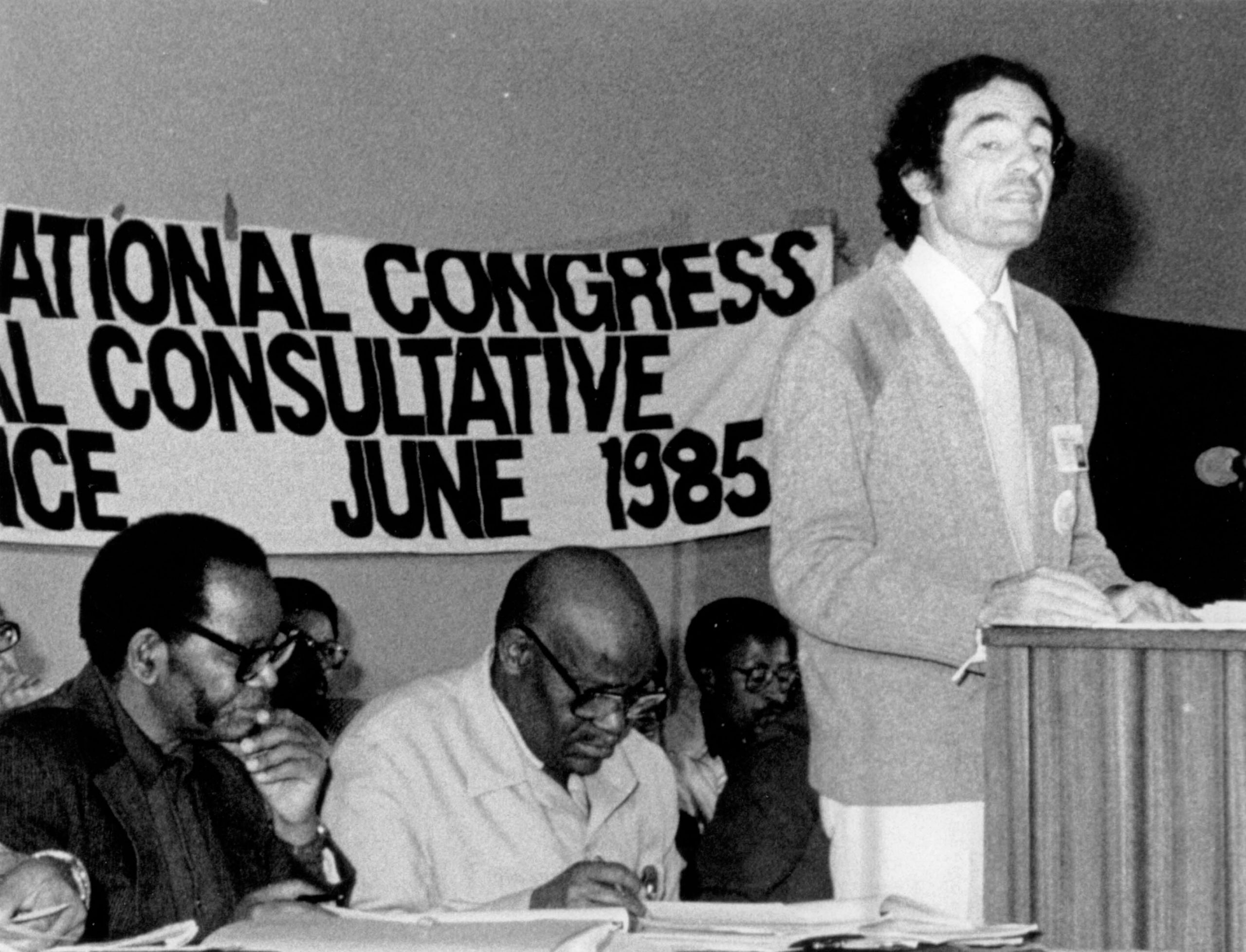 Albie Sachs speaks at the ANC National Consultative Conference, Kabwe, 1985. Sachs argued for the adoption of a Code of Conduct guaranteeing due process for dealing with misconduct by ANC members, and guaranteeing that captured enemy agents would not be subjected to torture. Oliver Tambo and Tom Nkobi are seated to Sachs' left. Albie Sachs Collection, UWC Robben Island Museum Mayibuye Archives