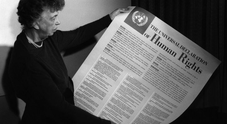 Eleanor Roosevelt reading the poster sized version of the Commission on Human Rights.